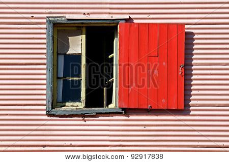 Old window with coloful red shutter in La Boca, Buenos Aires, Argentina