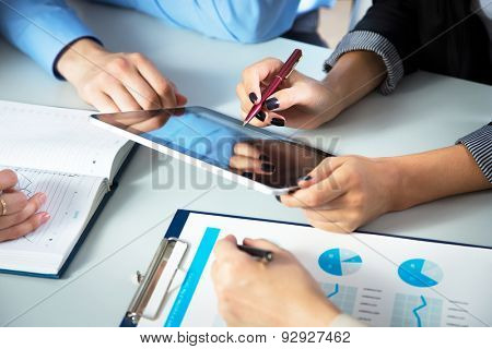 Businesspeople analyzing financial data in office