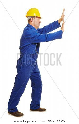 Isolated full body construction worker in boiler suit pushing an imaginary wall