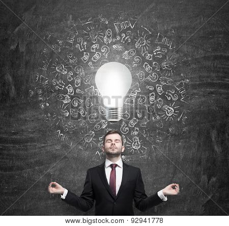 Meditating Young Businessman Thinking About The Light Bulb. A Concept Of The Brainstorm In Business