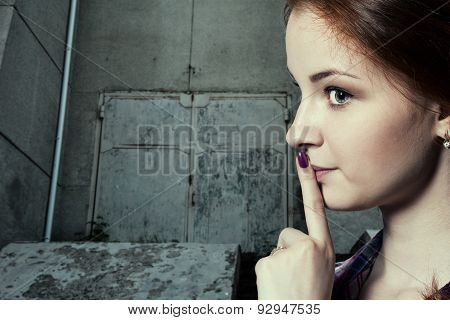 Psst - a beautiful girl with pigtails making a shushing gesture raising her finger to her lips as she asks for silence or secrecy portrait on vintage background old rusty door poster