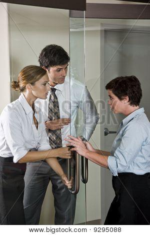 Three Office Workers At Door Of Boardroom