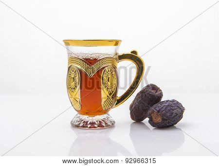 Middle eastern beverage and refreshment. Cup of black arabic tea and date fruits.