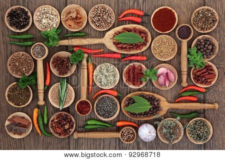 Herb and spice selection in wooden bowls, spoons and  loose over old oak background.