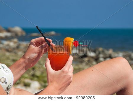 Woman with cocktail on the beach