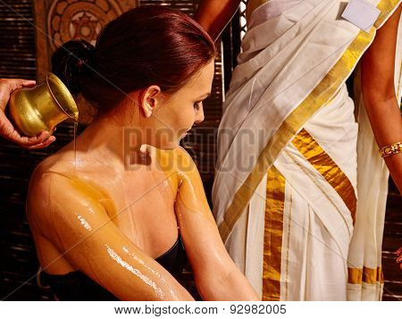 Young woman having pouring massage oil in ayurveda spa treatment.
