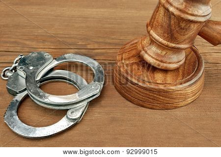 Judges Gavel And Handcuffs  On Wood Rough Background