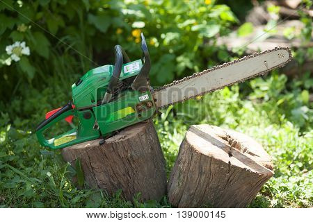 Green chainsaw tool on green blurred background.