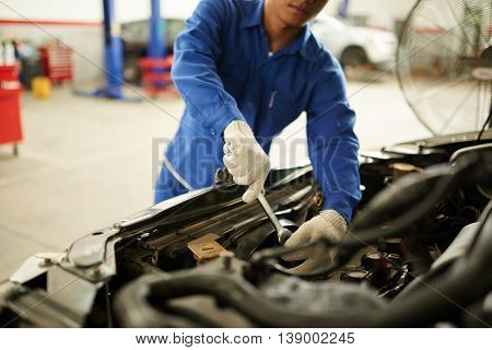 Cropped image of mechanic checking car transmission