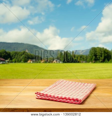 Empty table covered with checked tablecloth over beautiful landscape