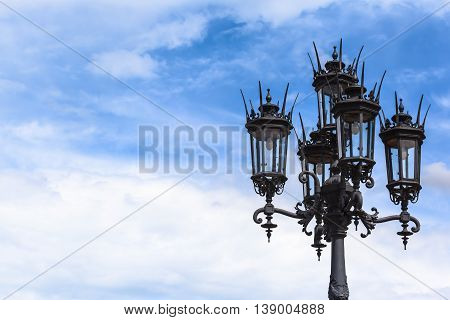 Historic shape black lamppost with five lanterns in front of blue sky and clouds background (copy space)