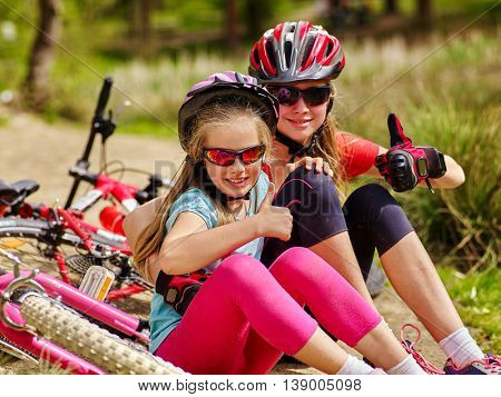 Bikes cycling family. Happy mother and daughter are sitting on country road near bicycles and shows thumb up.