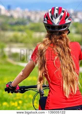 Back view of bikes cycling girl. Girl in red t-shirt rides bicycle. Girl in cycling. Cycling is good for health. Cyclist looking at city. Back to home.