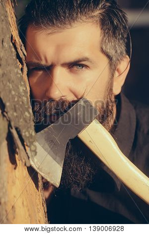 handsome bearded young man hipster with long beard and mustache has stylish hair on serious face sunny day outdoor holding sharp axe or ax on green natural background