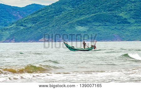 Hue, Vietnam - June 23rd, 2015: Fishermen out to sea in morning with boat curved nose as if to confront big waves offshore, although hard, but results much improved fishing income for people seas