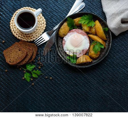 Fried egg in salami and baked potatoes. Submission of a frying pan with a cup of coffee and rye bread. Breakfast. The top view