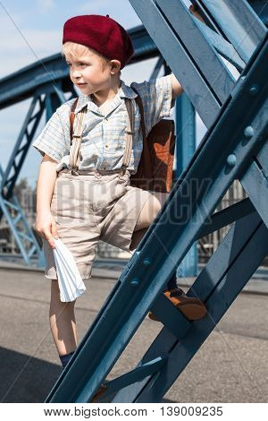 Retro styled cute boy at the way to - from school wear satchel, suspenders, shirt, shorts and red beret hat, play with paper airplane and climb at blue steel beam