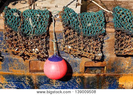 SCARBOROUGH ENGLAND - JULY 16: Fishing gear netting and buoy hanging off the side of a trawler. In Scarborough North Yorkshire England. On 16th July 2016.