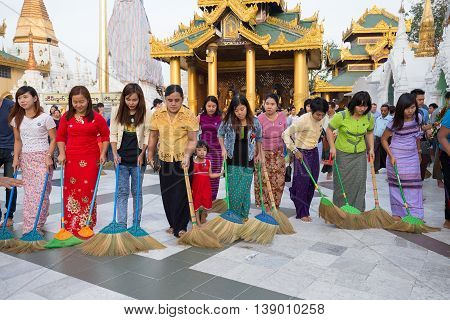 YANGON MYANMAR - JANUARY 9 2016: Unidentified group of pilgrims participate in a ceremony with brooms at the Shwedagon Pagoda. Shwedagon Pagoda is the most sacred Buddhist pagoda for the Burmese