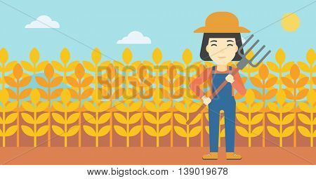 An asian female farmer holding a pitchfork. Smiling Farmer standing on the background of wheat field. Vector flat design illustration. Horizontal layout.