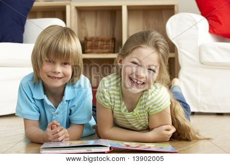 Two Young Children Reading Book at Home poster