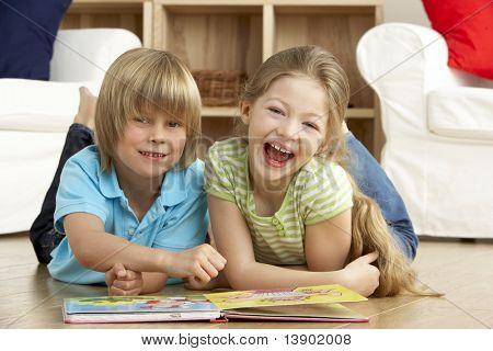Duas crianças lendo o livro em casa