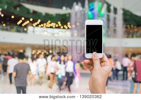 Smart phone with white screen in hand on blurred in shopping mall backgroundshopping online conceptshopping by smart phone