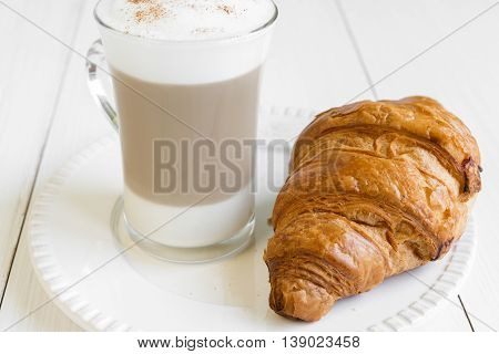 Croissant and glass of cafe latte on white plate and white table