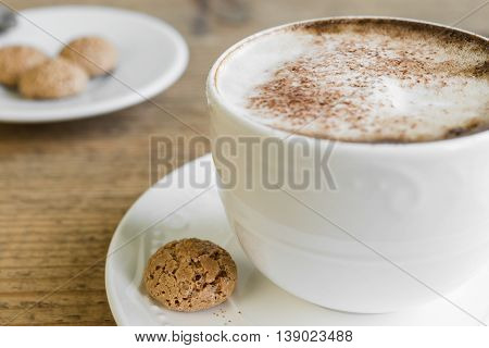 Cup of latte macchiato coffee with biscotti arranged on old rustic wooden table