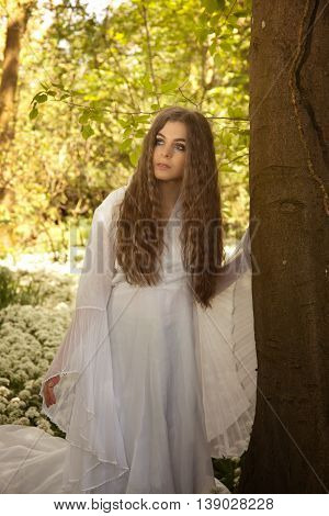 Beautiful woman wearing a long white dress leaning against a tree looking into the distance