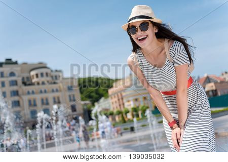 have a nice walk. Pleasant cheerful woman standing near fountain and expressing joy while walking