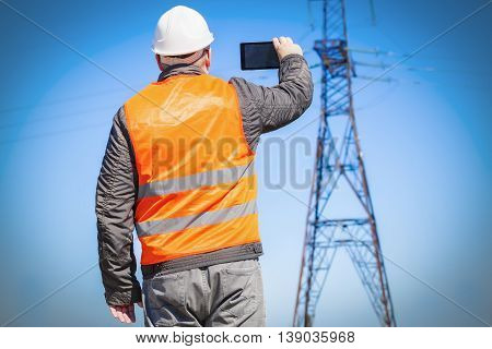 Electrician inspect the high-voltage power lines technical condition