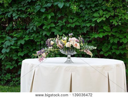 Beautiful flower composition outdoors. Wedding floristic decoration at white table, bouquet of colorful wildflowers and white roses in glass vase at green leaves background