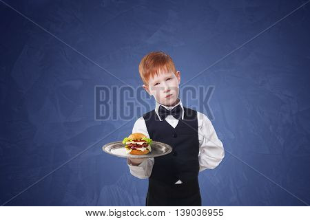 Little sad and tire waiter stands with tray serving hamburger. Redhead child boy in suit plays hardworking restaurant servant, gives burger at blue background