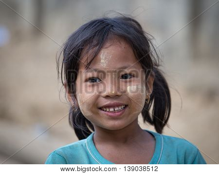 MRAUK-U MYANMAR - JANUARY 26 2016: Unidentified young Myanmar girl with thanaka on her smile face is happiness. Thanaka is a yellowish-white cosmetic paste made from ground bark.