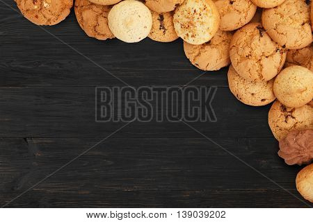 Cookies and sweet biscuits at black wood, background with copy space. Oatmeal and chocolate drops cookies border, dessert for tea.