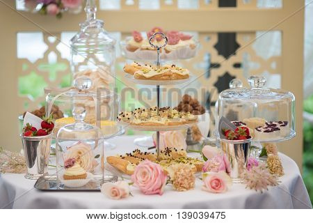 Dessert table for a party. Eclairs cake cupcakes sweetness and flowers