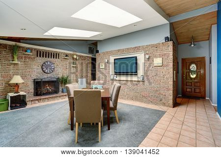 Light Spacious Dining Room With Stone Tile Wall And Built-in Fireplace