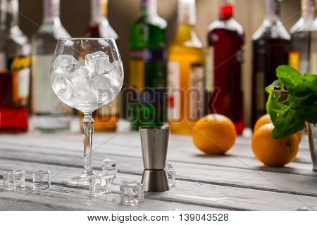 Bar jigger and wineglass. Glass full of ice cubes. Order whatever you want. Bartender's workplace in restaurant.