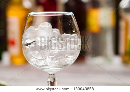 Ice cubes inside wineglass. Glass filled with ice. You need to cool down. Welcome to the pub.