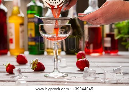 Red cocktail pours through sieve. Hand holding sieve over glass. Preparation of clover club. Fresh and sweet beverage.