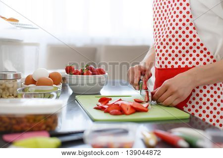 Young beautiful woman dressed in a white shirt and white red polka dot pinafore,engaged in the bright kitchen slicing red ripe strawberries to decorate cupcakes