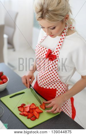 Young beautiful woman,blonde hair,light makeup and pink lipstick,wearing earrings,wearing a white t-shirt and white red polka dot pinafore,engaged in the bright kitchen cutting red strawberries to decorate cakes