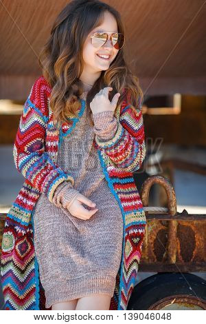 Cute teen girl, caucasian appearance, brunette with long curly hair, wearing sun glasses, wearing a long coat knitted red and blue, spending time in the countryside in the fresh air in summer, standing near a rusty truck for transportation of boats