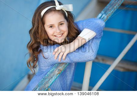 Cute teen girl, caucasian appearance, brunette with long curly hair and brown eyes, wearing a blue jacket, color white ribbon tied around, posing sitting on a ladder on a blue background outdoors in spring.