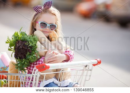 The little blonde girl with black and pink bow on head,wearing sun glasses with a blue frame in a red plaid shirt,sitting in a cart filled with groceries at the supermarket ,clutching a paper bag with the loaves and greens