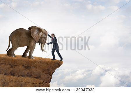 business strength concept businessman pushed to the edge of a cliff by an elephant