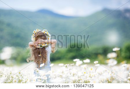 Cute little girl with curly, long hair,dressed in light blue overalls and a blue shirt with white polka dots, on the head wears a wreath of white wildflowers posing on a blooming white daisies field in a mountainous area in the summer,rear view