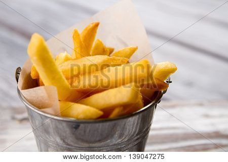 Bucket with yellow fries. French fries and paper. Product that harms your health. Eat less junk food.
