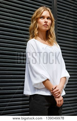 Portrait of brooding blonde girl in white blouse near gray wall outdors